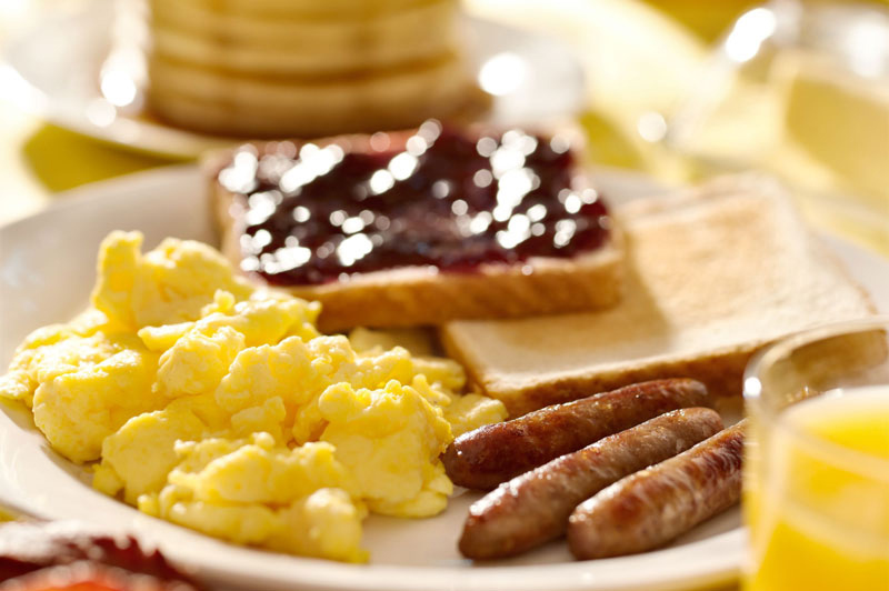 Breakfast with scrambled eggs, sausage links, toast and orange juice